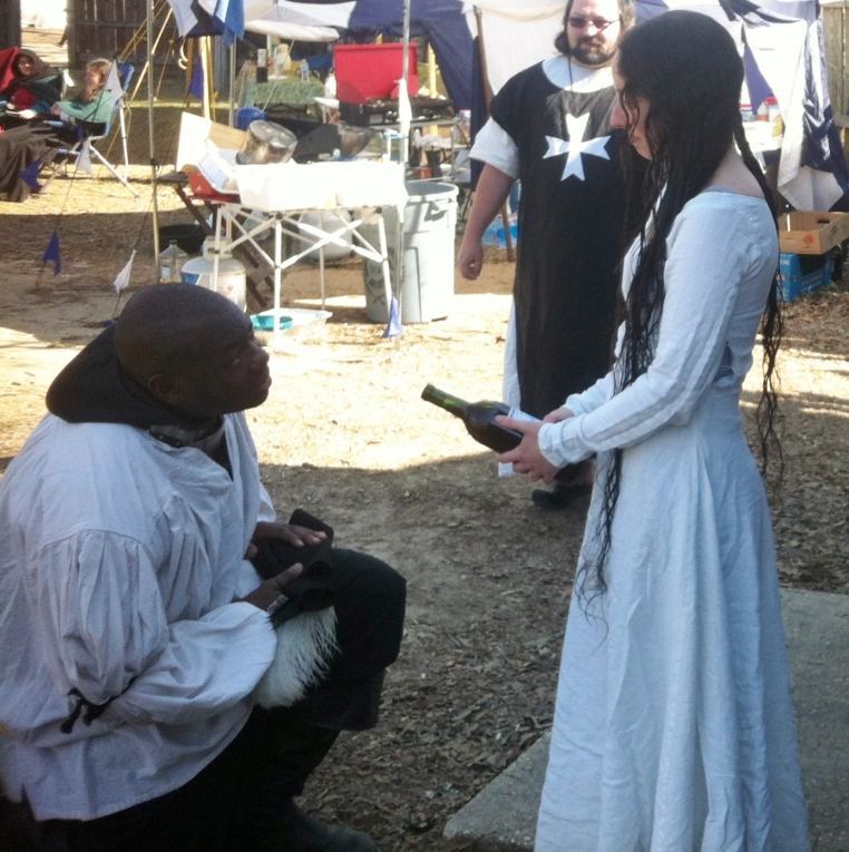 Davius St. Jacques, former Queens' Champion of Rapier, presents his winnings from a tournament to Queen Thyra outside the East Kingdom Cabin at last year's Gulf Wars