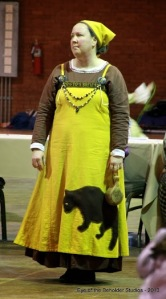 "Ella de Caleys represented the Boston Bruins with a bear on the front and back of the dress, and another on the headscarf, hockey-puck-ish brooches, and two whittled wooden hockey sticks hanging from the necklace. Brown wool trim around the top of the apron dress had ""Boston Bruins"" runes embroidered in harvest gold wool thread. The color scheme was the Boston Bruins original colors in 1924, and the bear that was enlarged from their original bear motif. The necklace includes beads of glass, wood, stone, metal, and fresh water pearls, all in team colors.  Alec Craig whittled the hockey sticks."