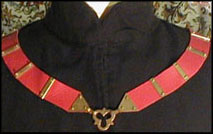 A red livery collar. The regalia of the Order of Defense is a white livery collar.
