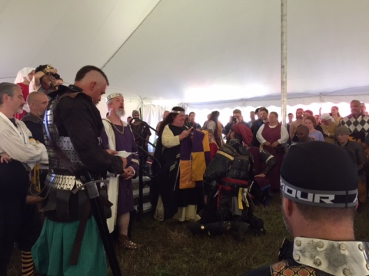 Her Majesty Avalina presents the East Kingdom Unbelts Team with their tabards.