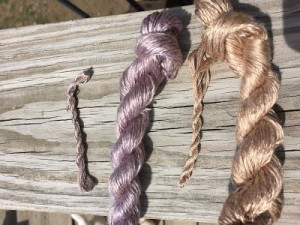 Commercial and handmade silk skeins. The purple is dyed with alkanet root, the pale brown with black walnut hulls