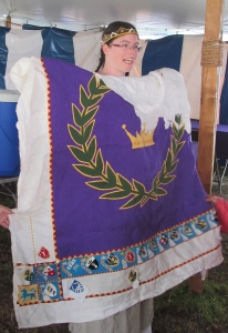 Baroness Jeanne displays the Kings' wallhanging during Pennsic 2017.