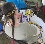 Baroness Jeanne at work on the Queens' wallhanging during Pennsic 2017.