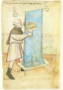 Peter Berber brushing a length of cloth with teasels. From the Mendel Hausbüch, 1425, Nuremberg City Library. Amb. 317.2° Folio 6 verso